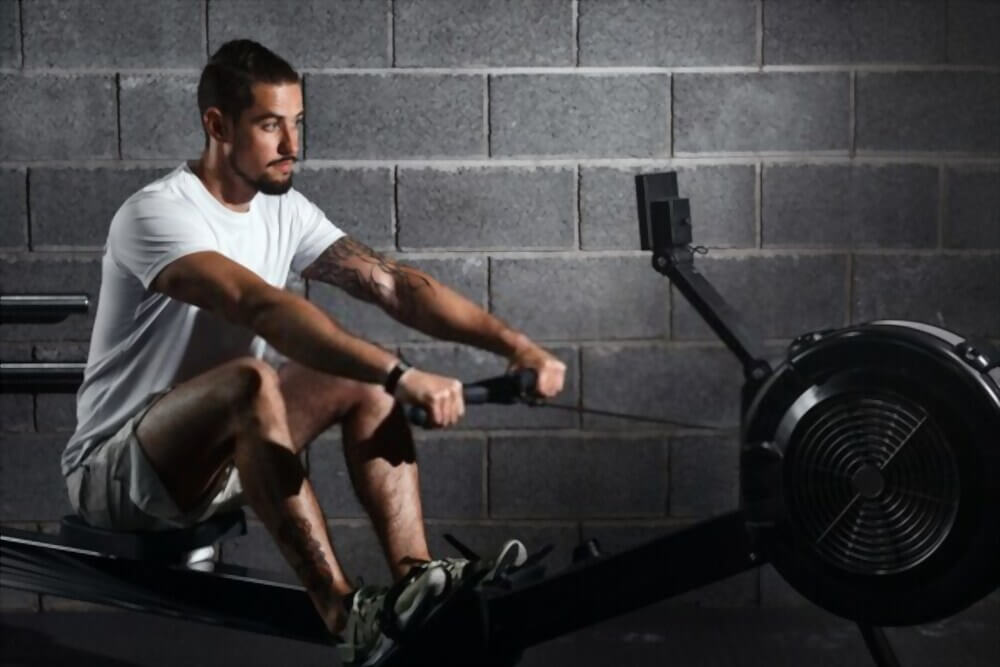 Fitness young man using rowing machine